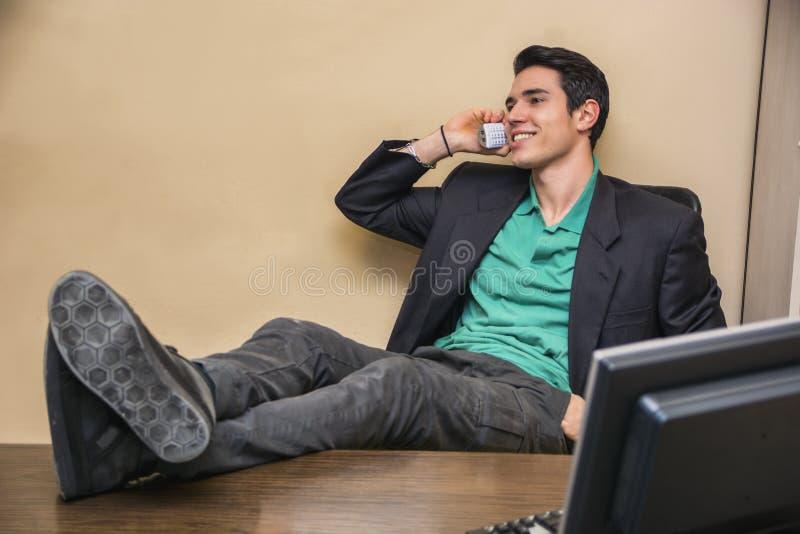 Hombre de negocios joven hermoso sonriente en el escritorio en el teléfono foto de archivo
