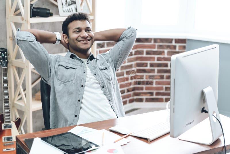 Hombre de negocios joven indio Work en el ordenador en la tabla imagen de archivo