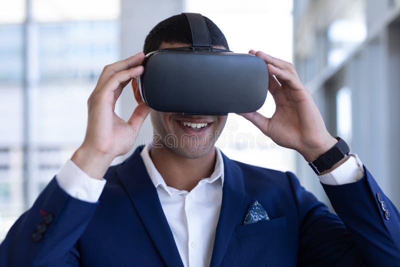 Hombre de negocios joven de la raza mixta que usa las auriculares de la realidad virtual en oficina moderna fotografía de archivo