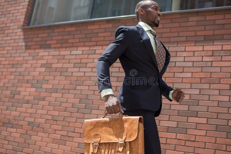 Hombre de negocios joven negro africano que corre en una ciudad imagenes de archivo