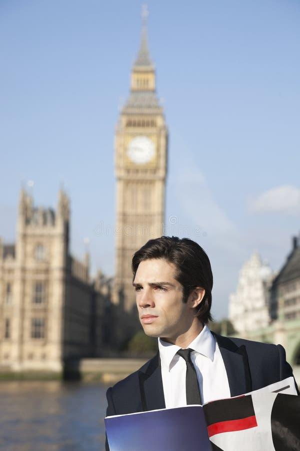 Hombre de negocios joven pensativo con el libro contra la torre de reloj de Big Ben, Londres, Reino Unido fotos de archivo