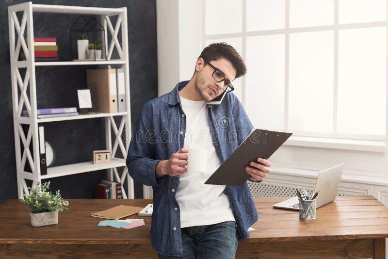 Hombre de negocios joven pensativo que habla en móvil y que lee documentos fotos de archivo