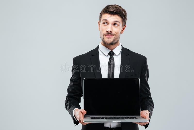 Hombre de negocios joven pensativo que lleva a cabo el ordenador portátil y el pensamiento de la pantalla en blanco imagenes de archivo