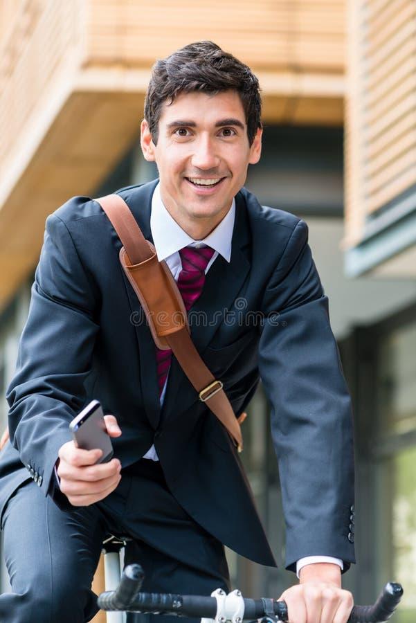 Hombre de negocios joven polivalente que monta una bicicleta para trabajar foto de archivo