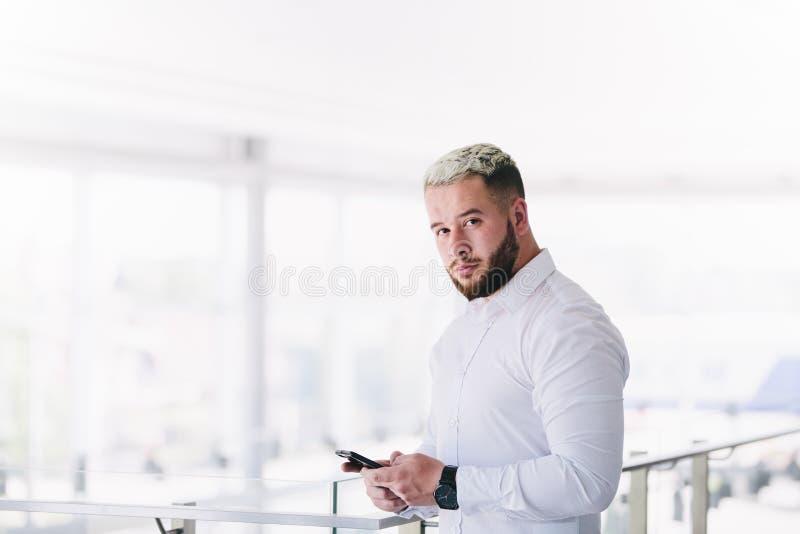 Hombre de negocios joven Posing While Using Smartphone en la rotura fotos de archivo