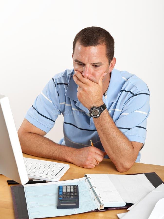 Hombre de negocios joven preocupante en el escritorio imagenes de archivo