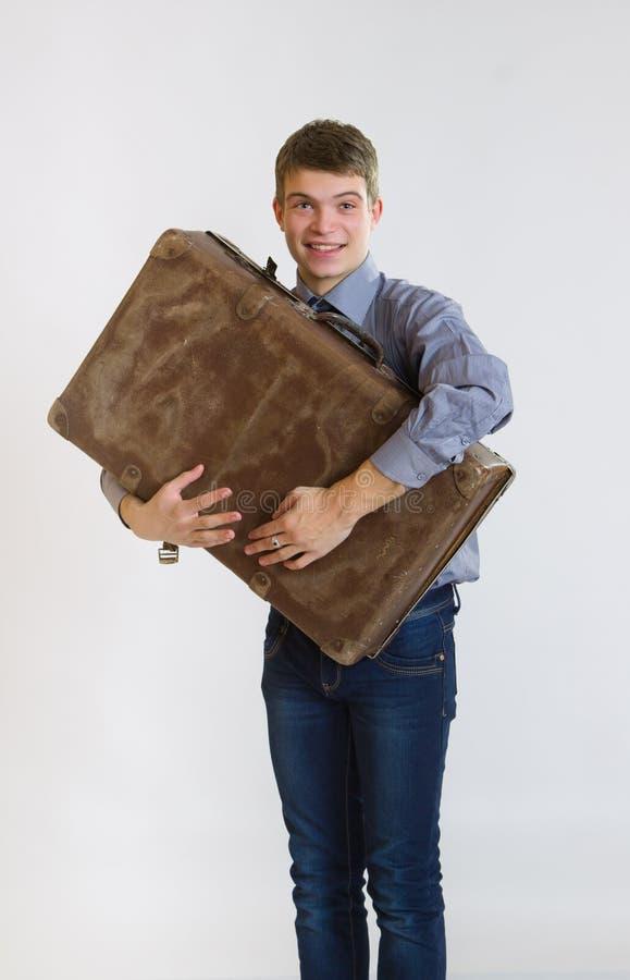 Hombre de negocios joven que abraza su maleta vieja fotografía de archivo