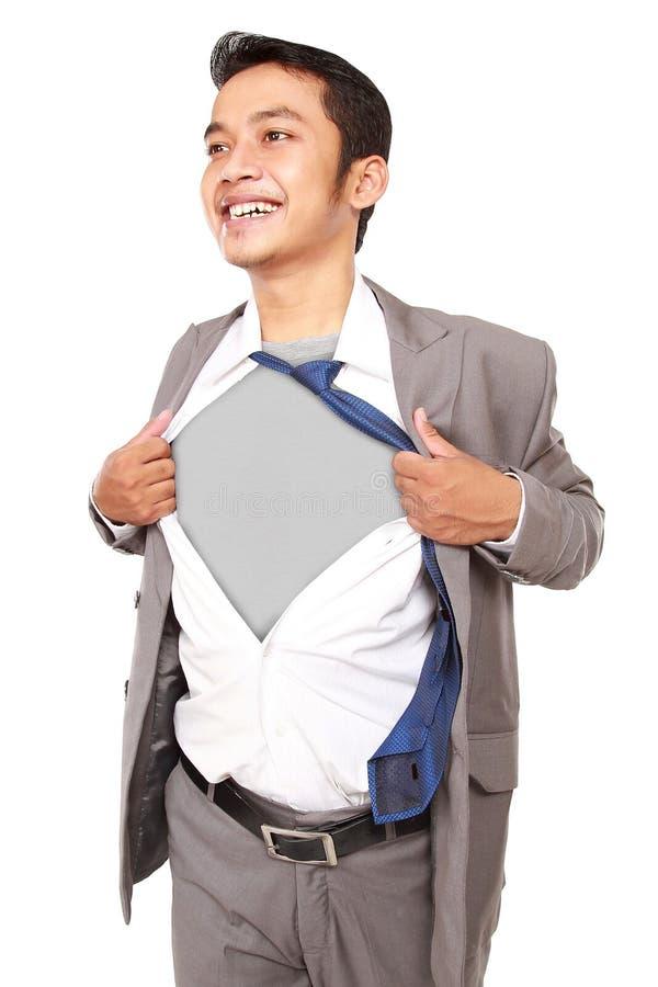 Hombre de negocios joven que actúa como un superhéroe y que rasga su camisa fotos de archivo