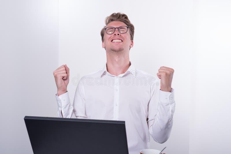 Hombre de negocios joven que anima su éxito mientras que trabaja en el ordenador portátil imágenes de archivo libres de regalías