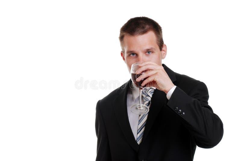Hombre de negocios joven que bebe el vino rojo foto de archivo libre de regalías