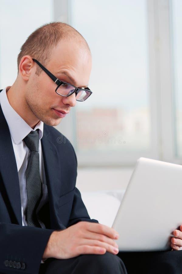 Hombre de negocios joven que busca con el ordenador portátil en Internet imágenes de archivo libres de regalías