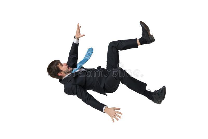 Hombre de negocios joven que cae abajo en caída libre Aislado en el fondo blanco imagenes de archivo
