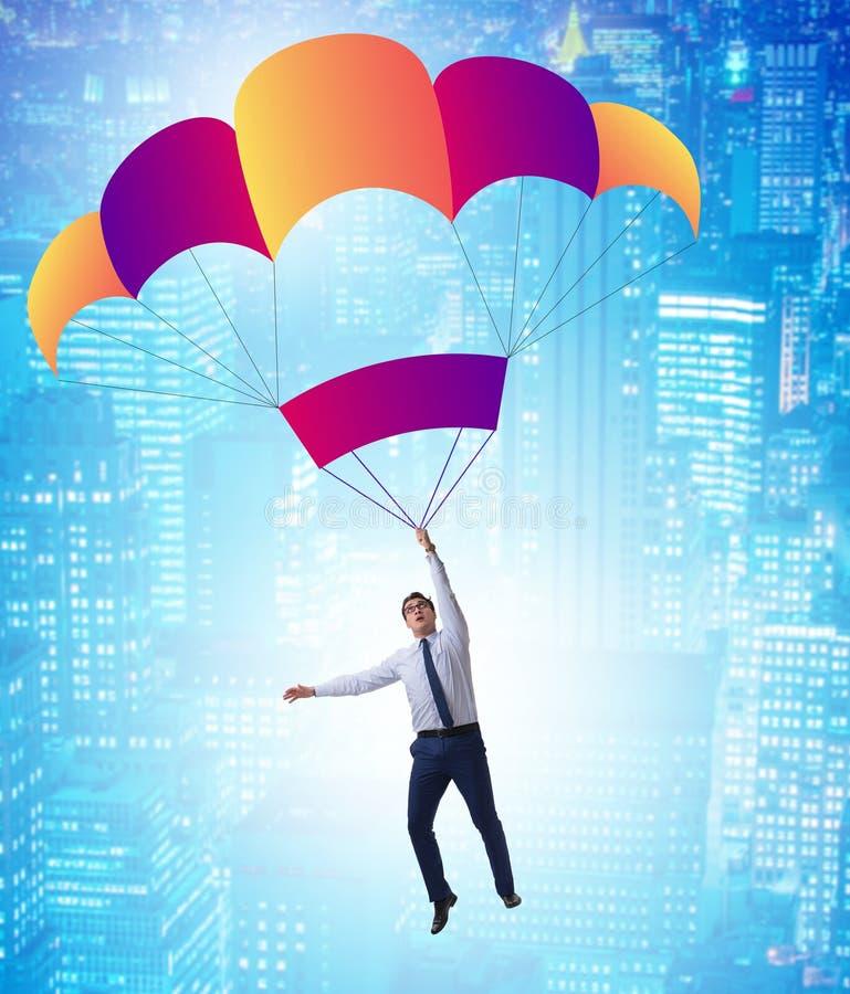 Hombre de negocios joven que cae en el paraca?das en concepto del negocio imagenes de archivo