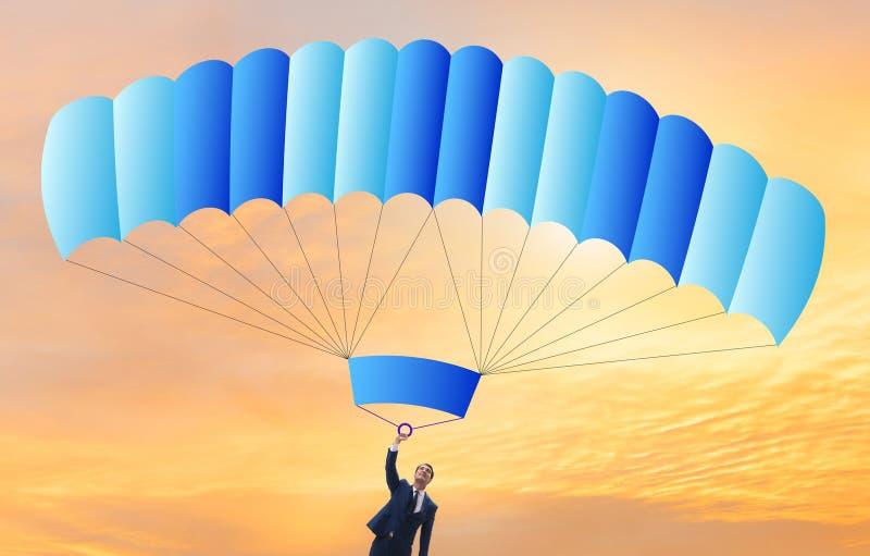 Hombre de negocios joven que cae en el paraca?das en concepto del negocio foto de archivo libre de regalías