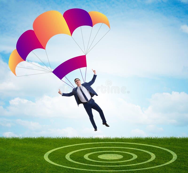 Hombre de negocios joven que cae en el paraca?das en concepto del negocio imágenes de archivo libres de regalías