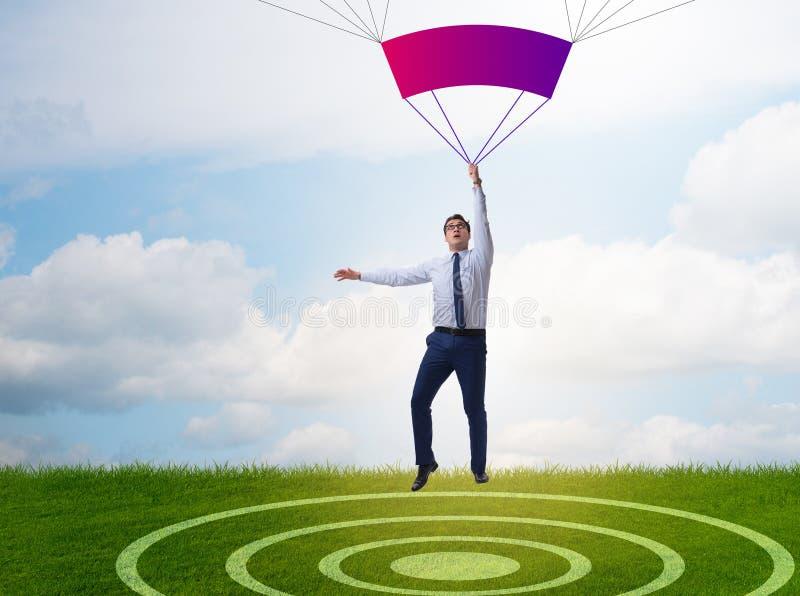Hombre de negocios joven que cae en el paraca?das en concepto del negocio fotos de archivo