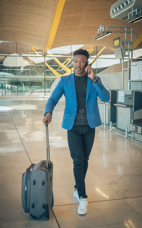 Hombre de negocios joven que camina en el aeropuerto que habla por el teléfono imagen de archivo