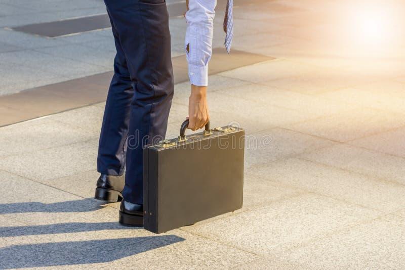 Hombre de negocios joven que coloca con el suyo la parte posterior que lleva una cartera c imágenes de archivo libres de regalías