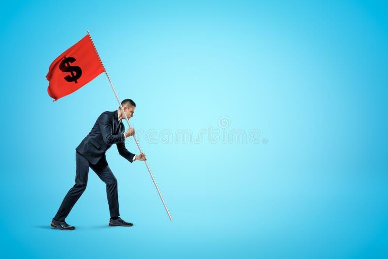 Hombre de negocios joven que coloca la bandera roja de la muestra de dólar en fondo azul imágenes de archivo libres de regalías