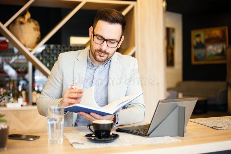 Hombre de negocios joven que comprueba orden del día diario en una libreta mientras que se sienta en una cafetería moderna imagen de archivo libre de regalías