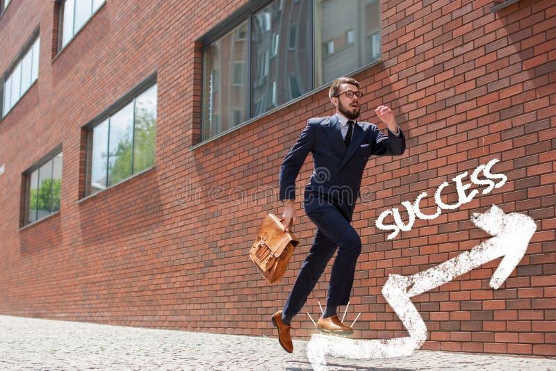 Hombre de negocios joven que corre en una calle de la ciudad foto de archivo libre de regalías