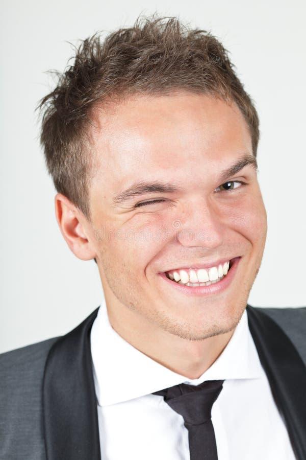 Hombre de negocios joven que da un guiño fotografía de archivo libre de regalías