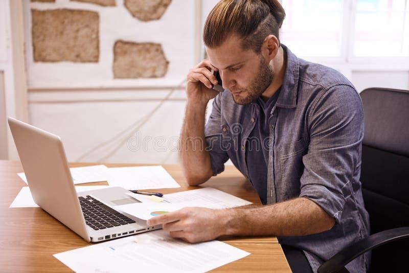 Hombre de negocios joven que discute notas sobre el teléfono foto de archivo