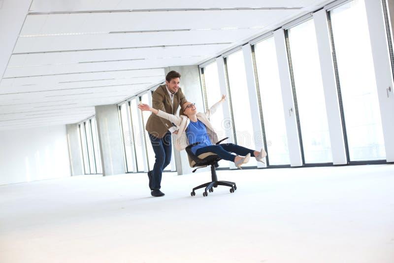 Hombre de negocios joven que empuja al colega femenino en silla en la oficina vacía imagenes de archivo