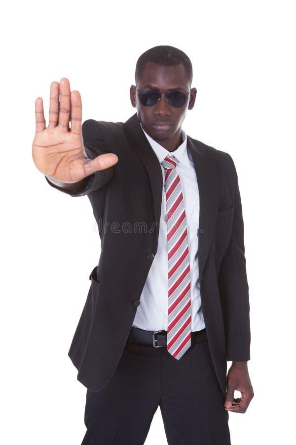 Hombre de negocios joven que gesticula la muestra de la parada imagen de archivo libre de regalías