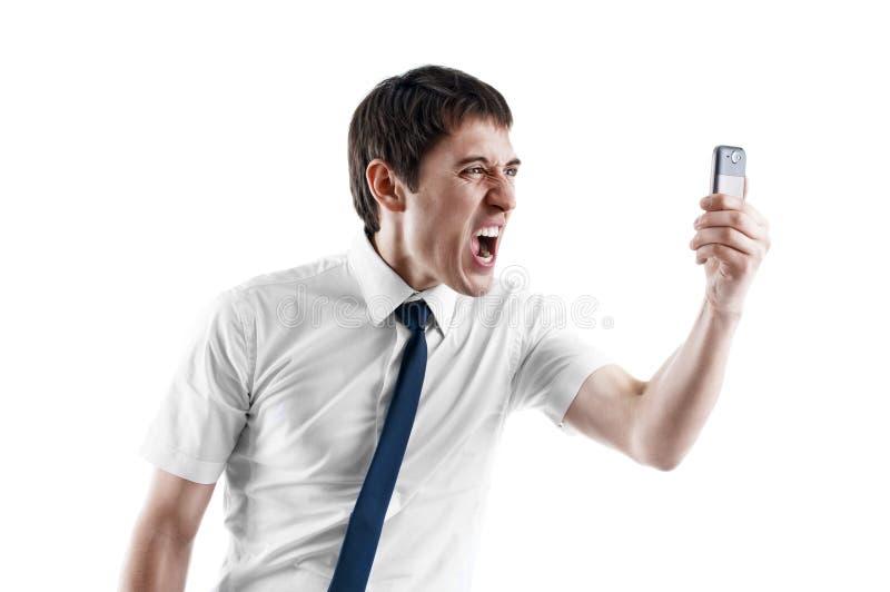 Hombre de negocios joven que grita en su teléfono celular fotos de archivo