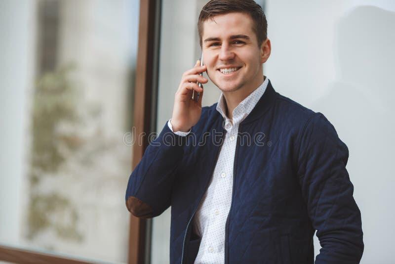 Hombre de negocios joven que habla en el teléfono móvil al aire libre imagen de archivo libre de regalías