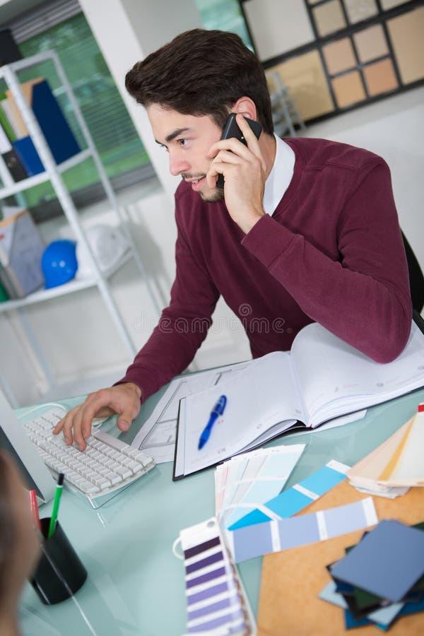 Hombre de negocios joven que habla en el teléfono móvil en oficina fotos de archivo libres de regalías