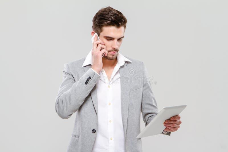 Hombre de negocios joven que habla en el teléfono móvil y que usa la tableta imágenes de archivo libres de regalías