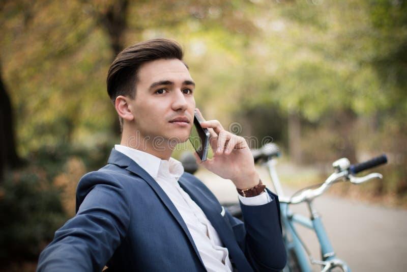Hombre de negocios joven que habla en smartphone al aire libre en un parque fotografía de archivo