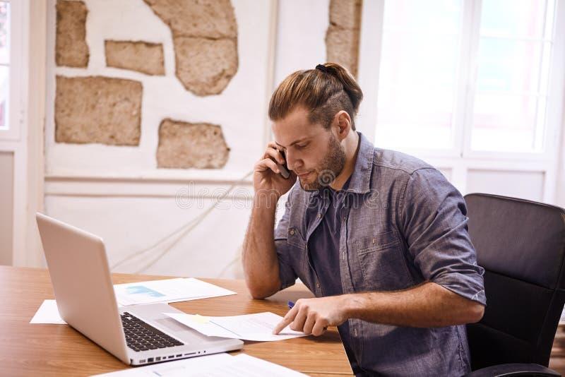 Hombre de negocios joven que habla en su teléfono fotos de archivo libres de regalías