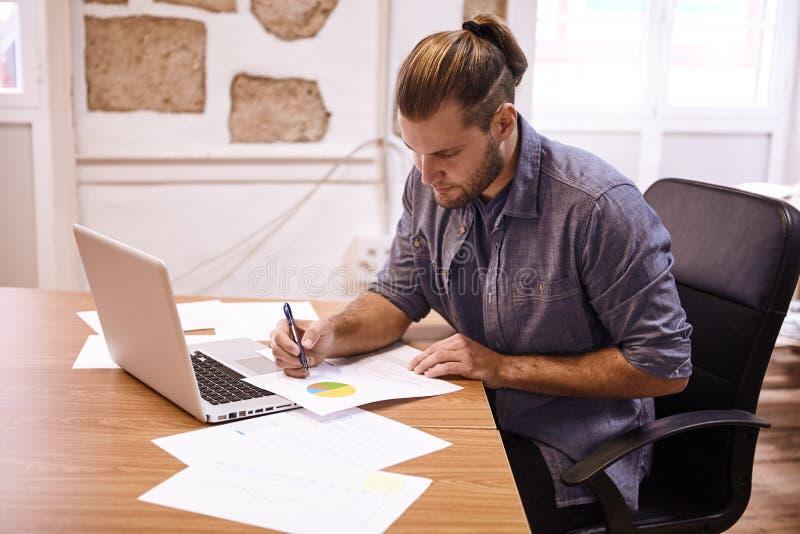 Hombre de negocios joven que hace notas en el escritorio fotos de archivo libres de regalías