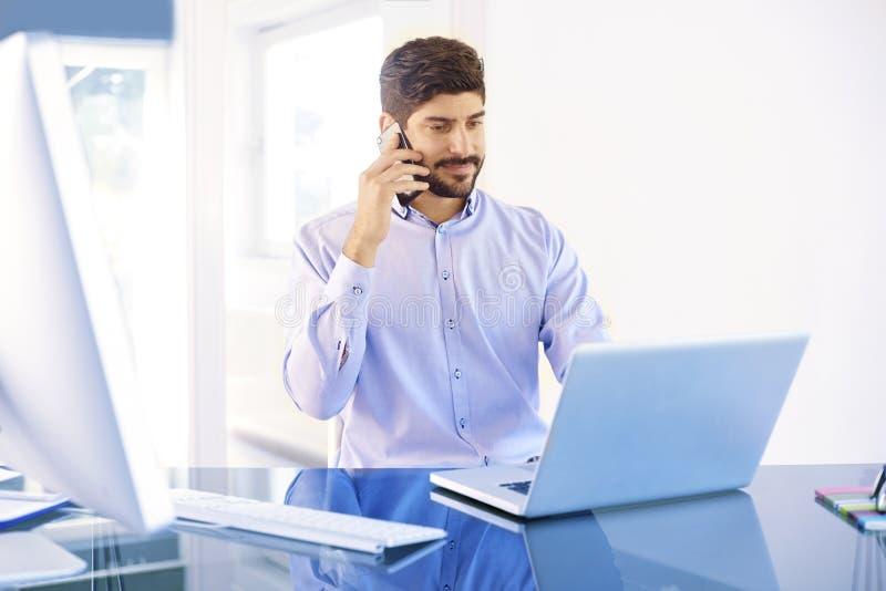 Hombre de negocios joven que hace una llamada mientras que trabaja en el ordenador portátil imagenes de archivo