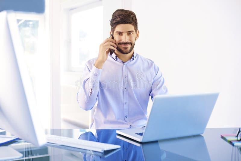 Hombre de negocios joven que hace una llamada mientras que trabaja en el ordenador portátil foto de archivo
