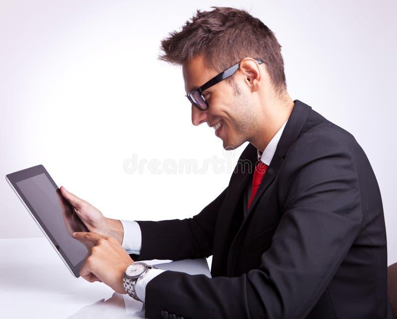 Hombre de negocios joven que hojea en su pista de la tablilla imagenes de archivo