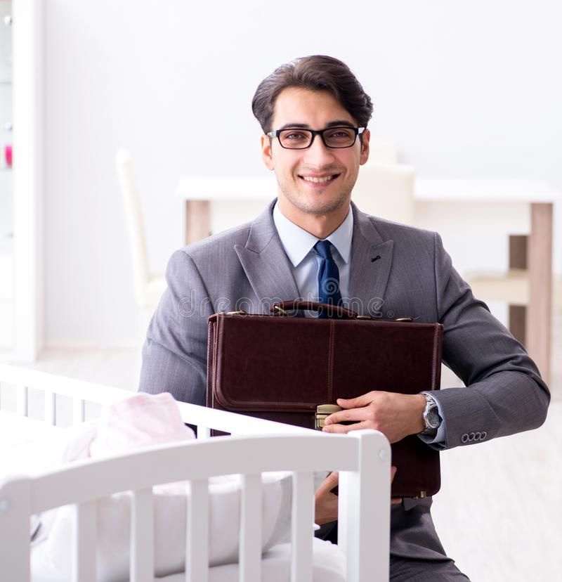 Hombre de negocios joven que intenta trabajar del hogar que cuida despu?s de reci?n nacido foto de archivo libre de regalías