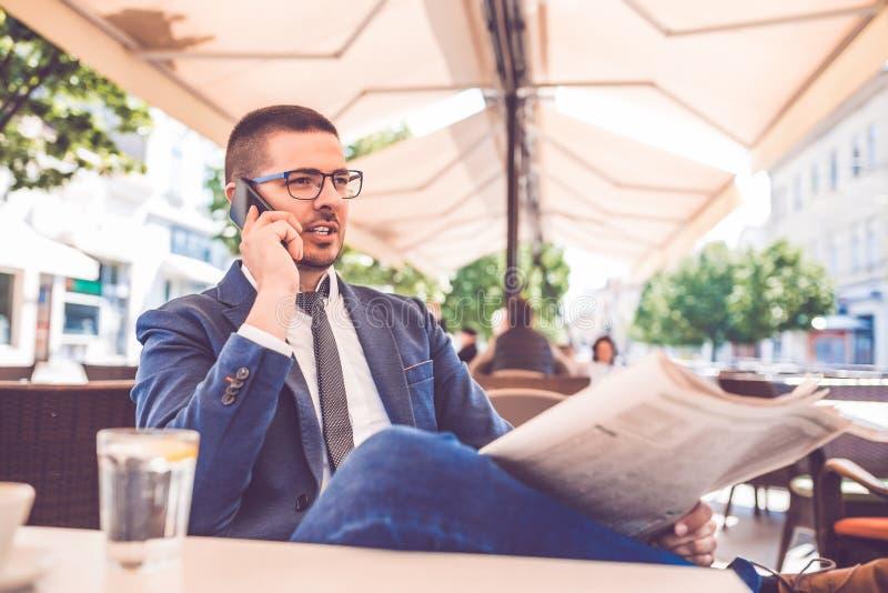 Hombre de negocios joven que lee los periódicos y que habla en el teléfono móvil fotos de archivo