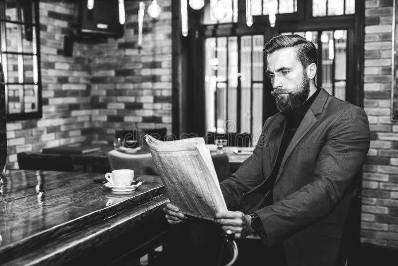Hombre de negocios joven que lee un periódico en la barra imágenes de archivo libres de regalías