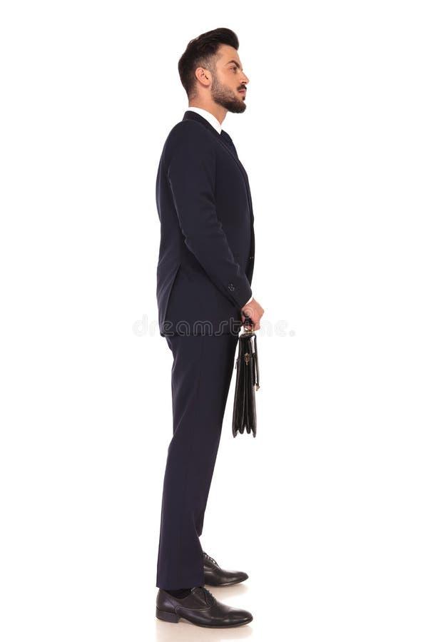 Hombre de negocios joven que lleva a cabo una cartera y una situación en línea imagen de archivo