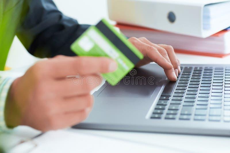Hombre de negocios joven que lleva a cabo una tarjeta y mecanografiar de crédito Compras en línea en Internet usando un ordenador imágenes de archivo libres de regalías