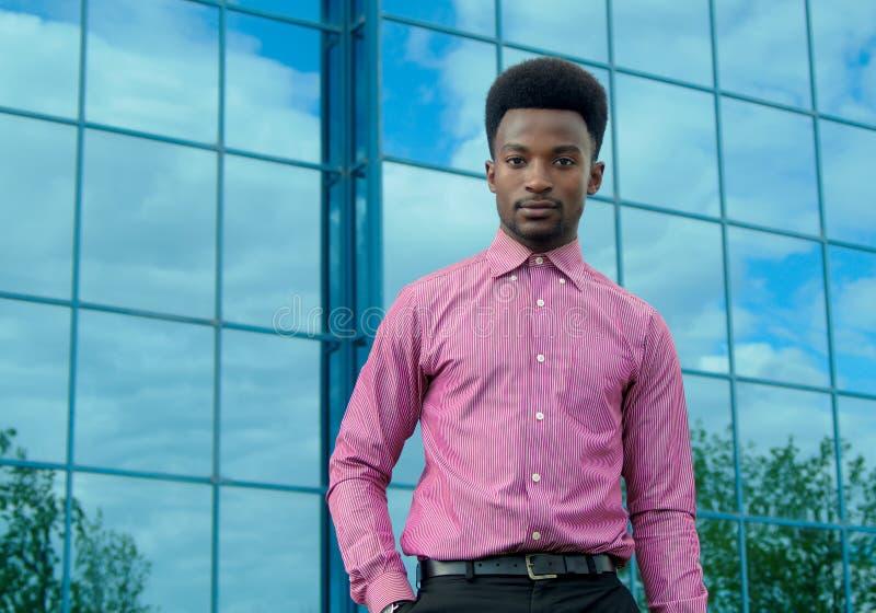 Hombre de negocios joven que lleva el fondo de cristal del edificio de oficinas de la camisa rosada imagen de archivo libre de regalías