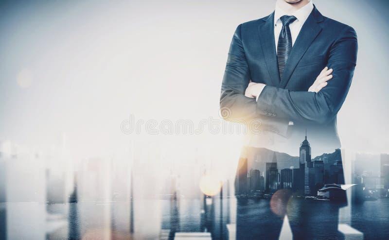 Hombre de negocios joven que lleva el traje moderno y la situación con sus brazos cruzados Exposición doble Ciudad horizontal, co foto de archivo libre de regalías