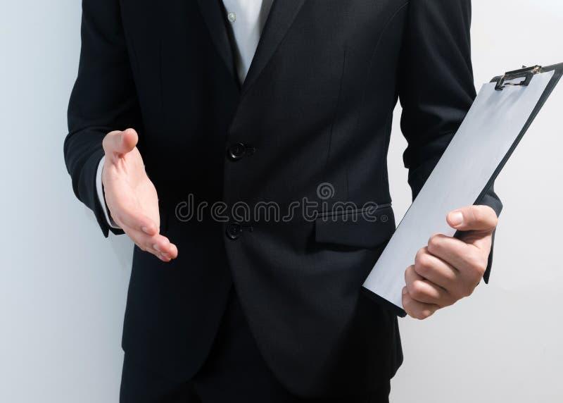 Hombre de negocios joven que lleva un traje mientras que lleva a cabo el tablero de la muestra y da el apretón de manos, trayecto fotos de archivo libres de regalías