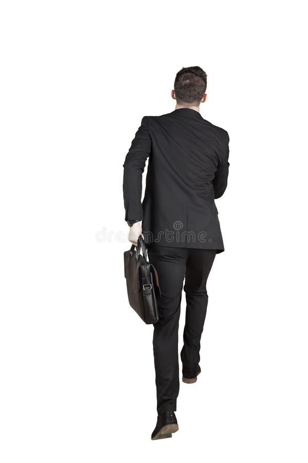 Hombre de negocios joven que lleva una cartera en estudio imagenes de archivo