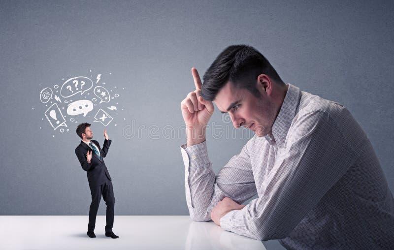 Hombre de negocios joven que lucha con el hombre de negocios miniatura imagen de archivo