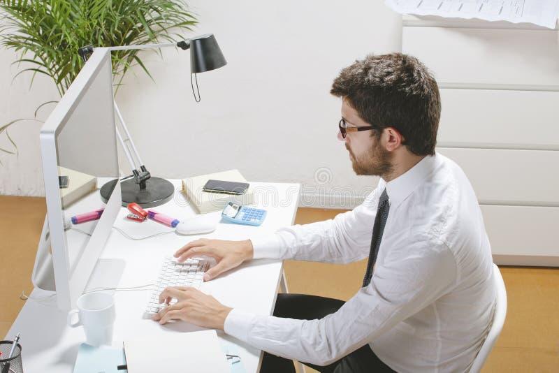 Hombre de negocios joven que mecanografía un ordenador en oficina. imagen de archivo libre de regalías